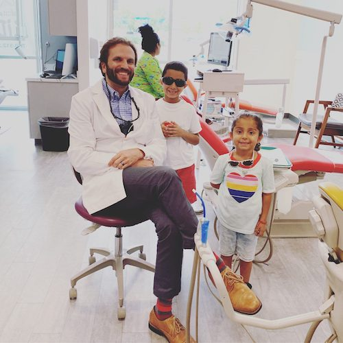 kids smiling with their dentist after teeth cleaning